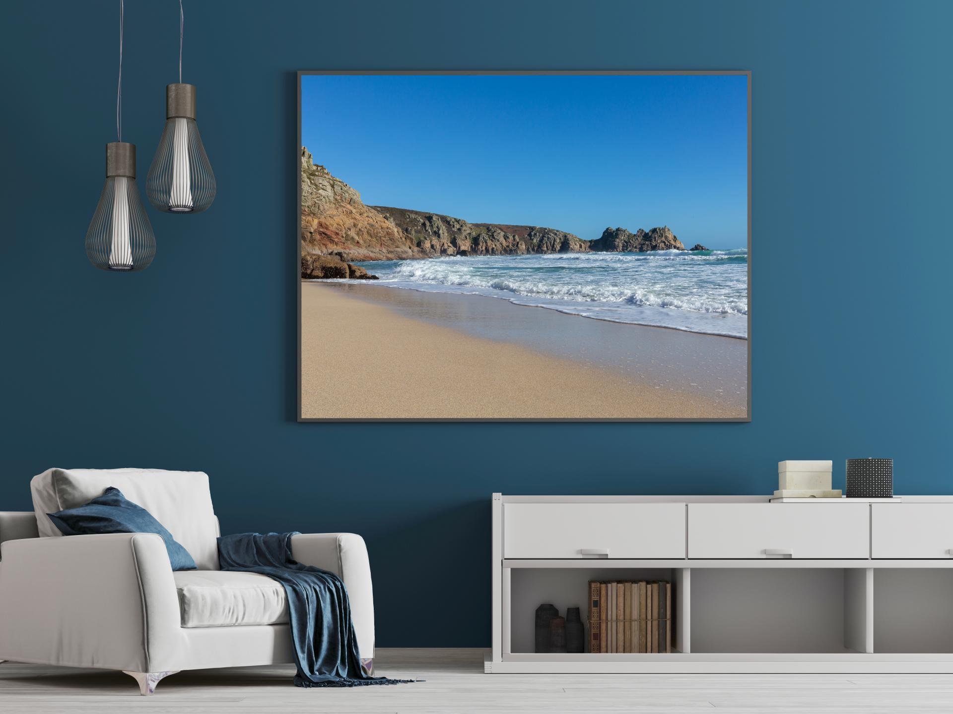 Waters edge at Porthcurno Beach, cornwall, with cliffs to the left curling around the image. Liane Ryan Photography