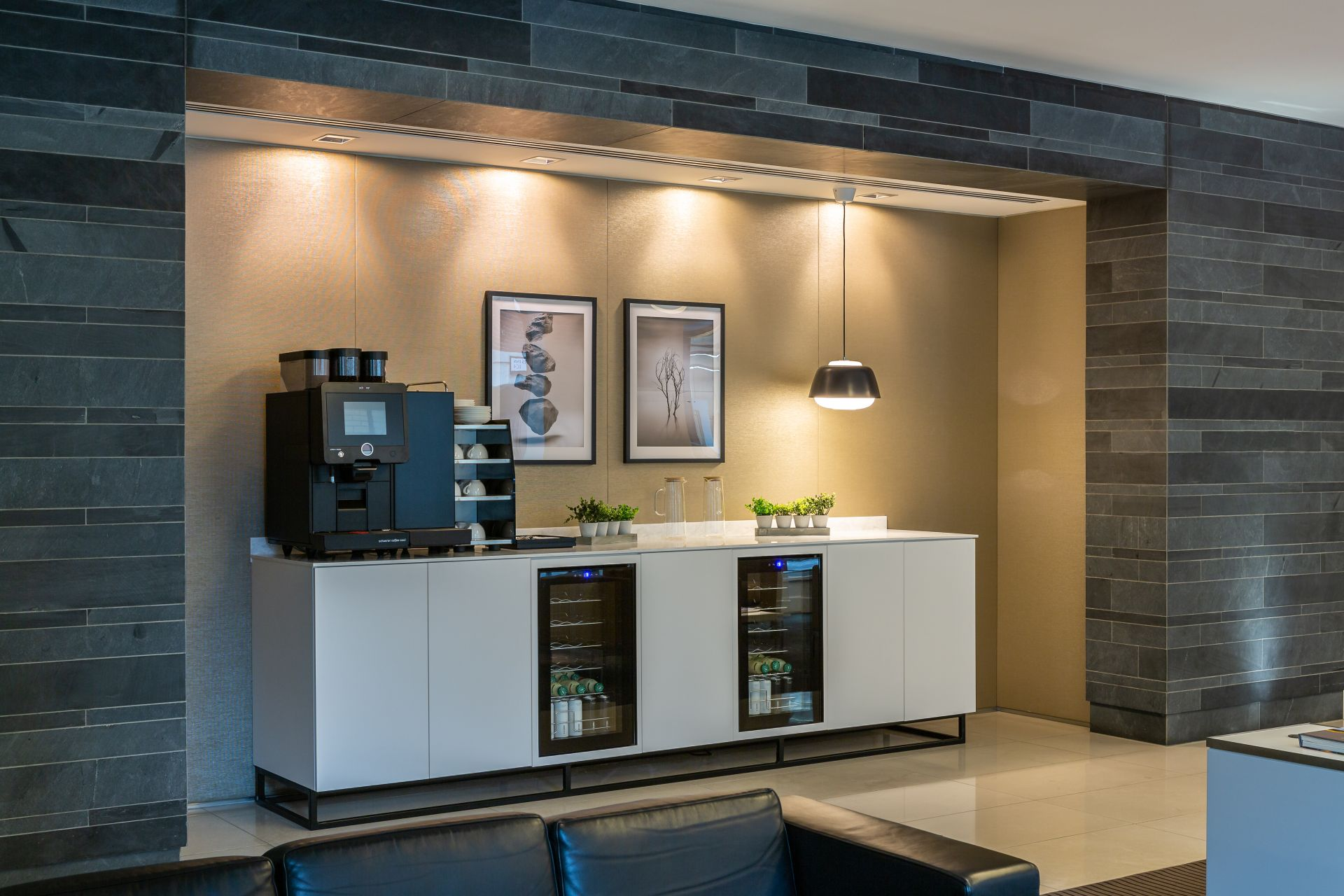 tea point in office showing two fridges under a counter with coffee machine